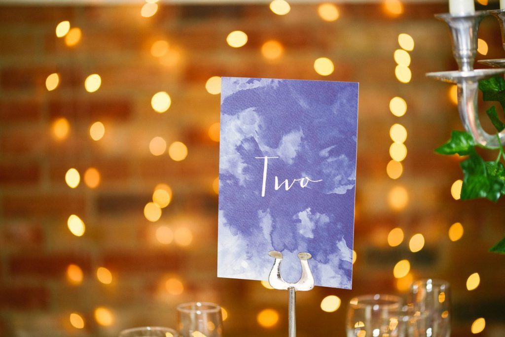 table number sign with fairy lights behind at rustic wedding