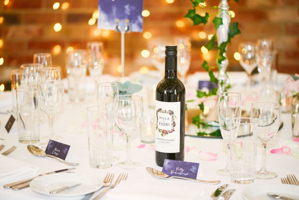 Bottle of wed wine on wedding table with fairy lights behind