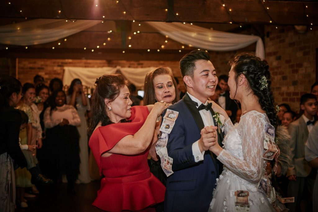 Guests pinning money to  filipino bride and groom during their first dance