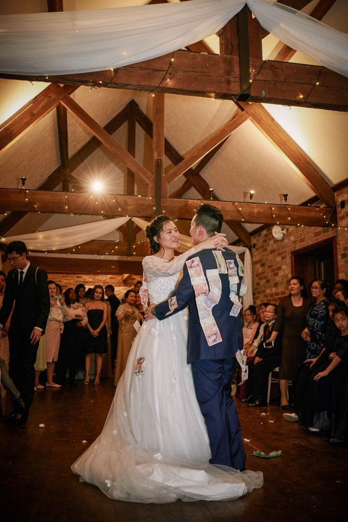 Bride and groom during filipino money dance at winter barn wedding