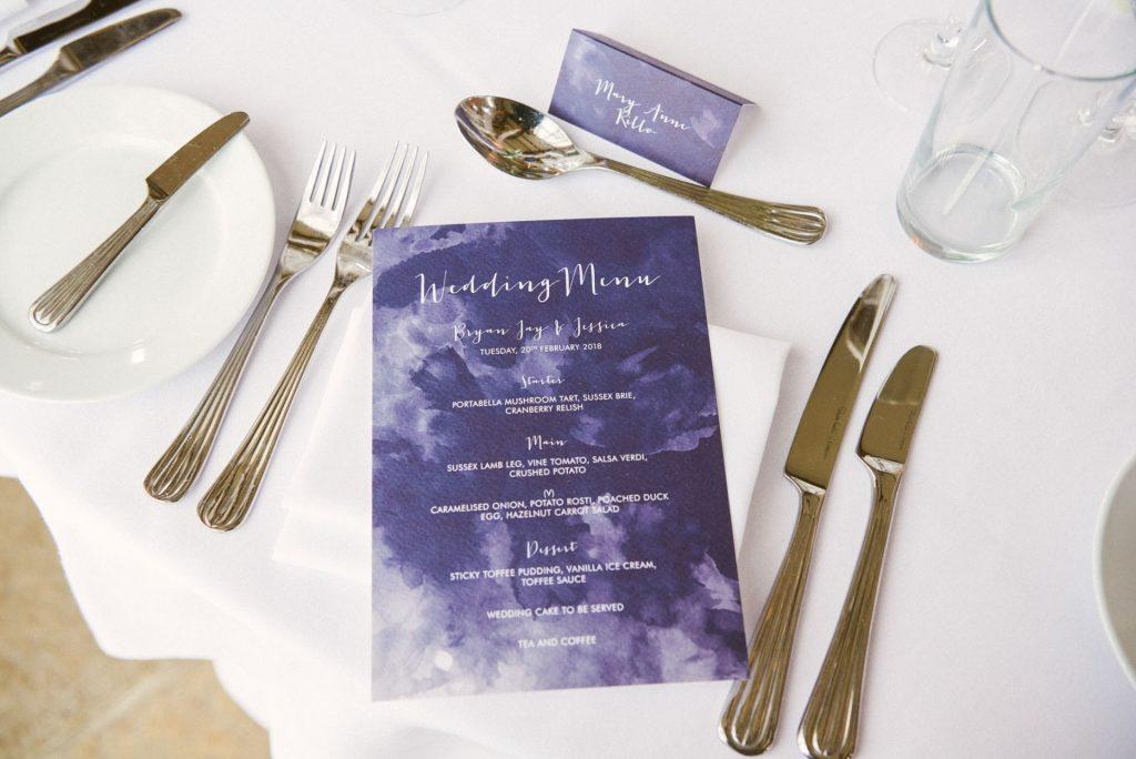 blue wedding menu on white table at Long Furlong Barn