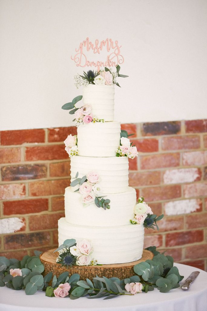White 5 tier wedding cake with flowers on it at rustic winter wedding