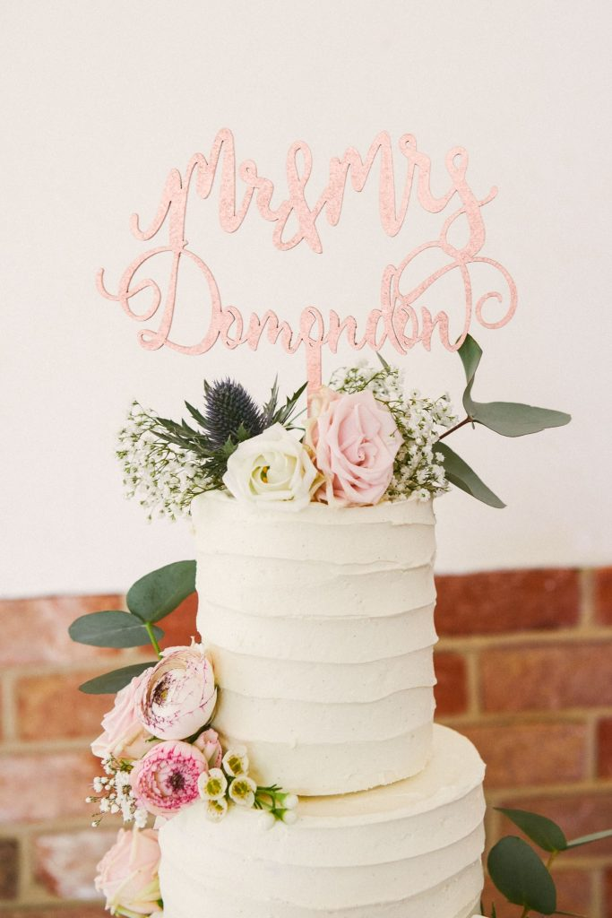 Personalised pink hand writing wedding cake topper on white cake