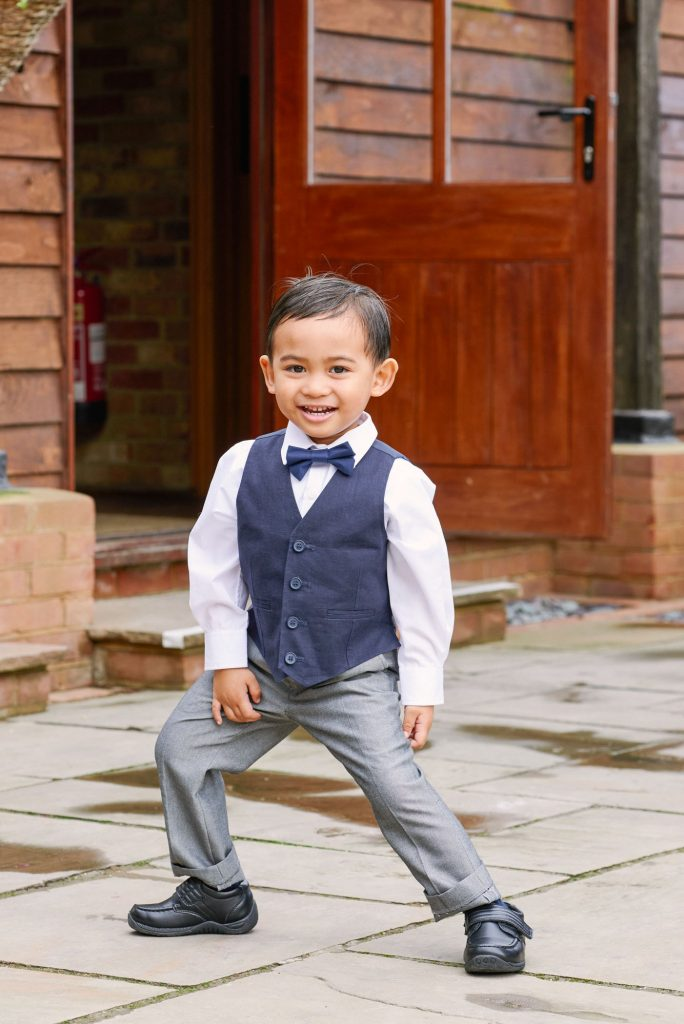 little kid smiling whilst playing in the courtyard during barn wedding