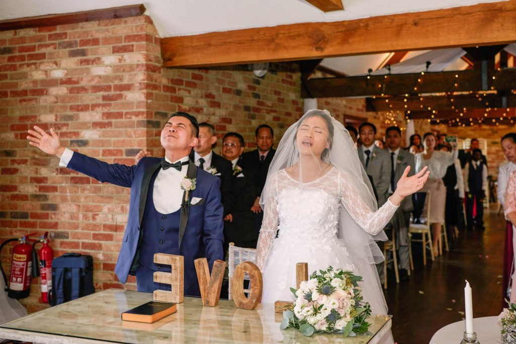 bride and groom signing hyms during their wedding ceremony at Long Furlong Barn