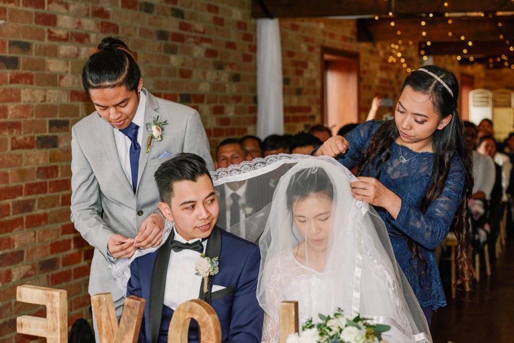 Bride and groom bringing The Candle, Cord, and Veil during filipino ceremony at Long Furlong Barn
