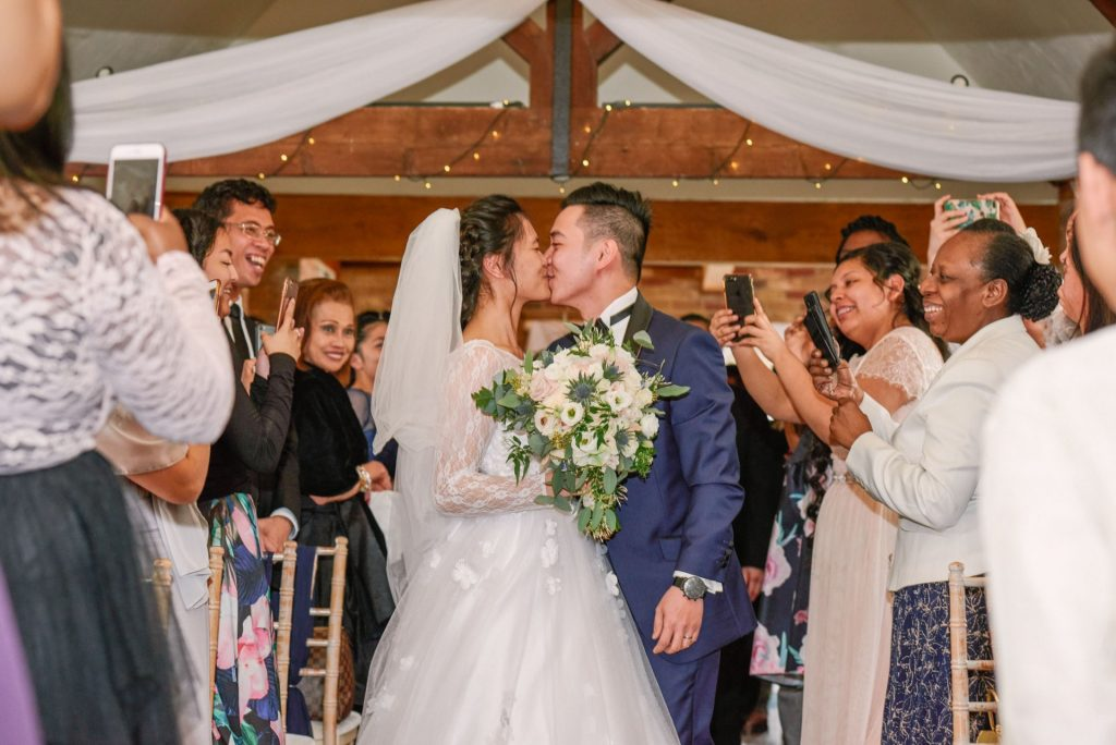 Bride and groom kissing during wedding ceremony at Long Furlong Barn