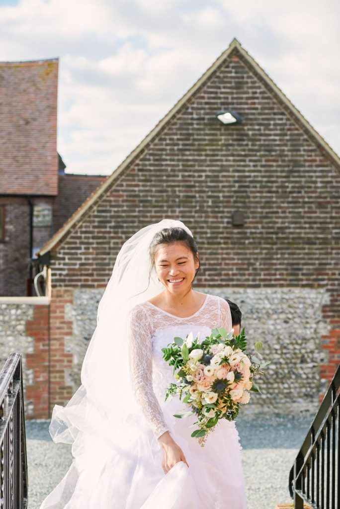 bride smiling whilst walking up step and holding flower bouquet