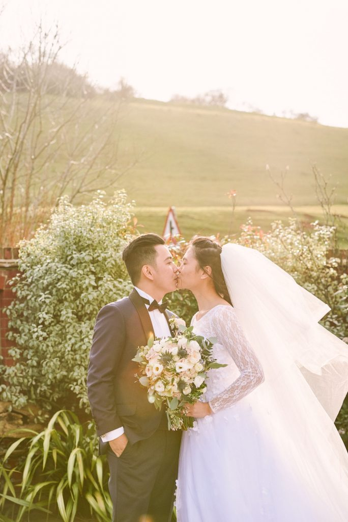 bride and groom kissing during sunset in a rustic garden