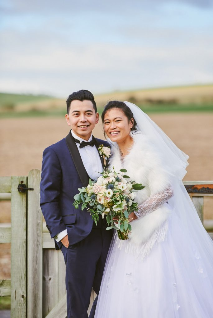 bride and groom smiling whilst stood in a field during rustic winter wedding