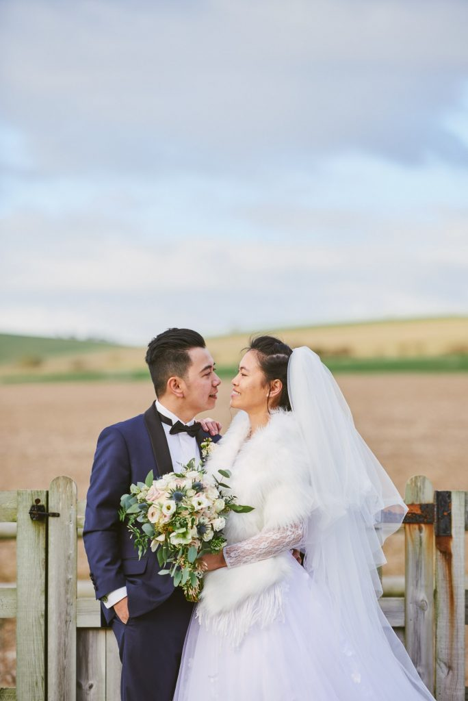 bride and groom stood in a field during rustic winter wedding at Long Furlong Barn