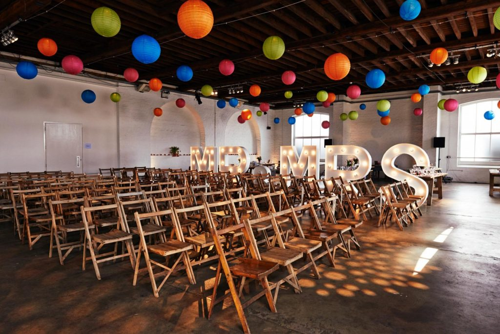 Interior of warehouse wedding with metal light up letters and colourful lantern decorations