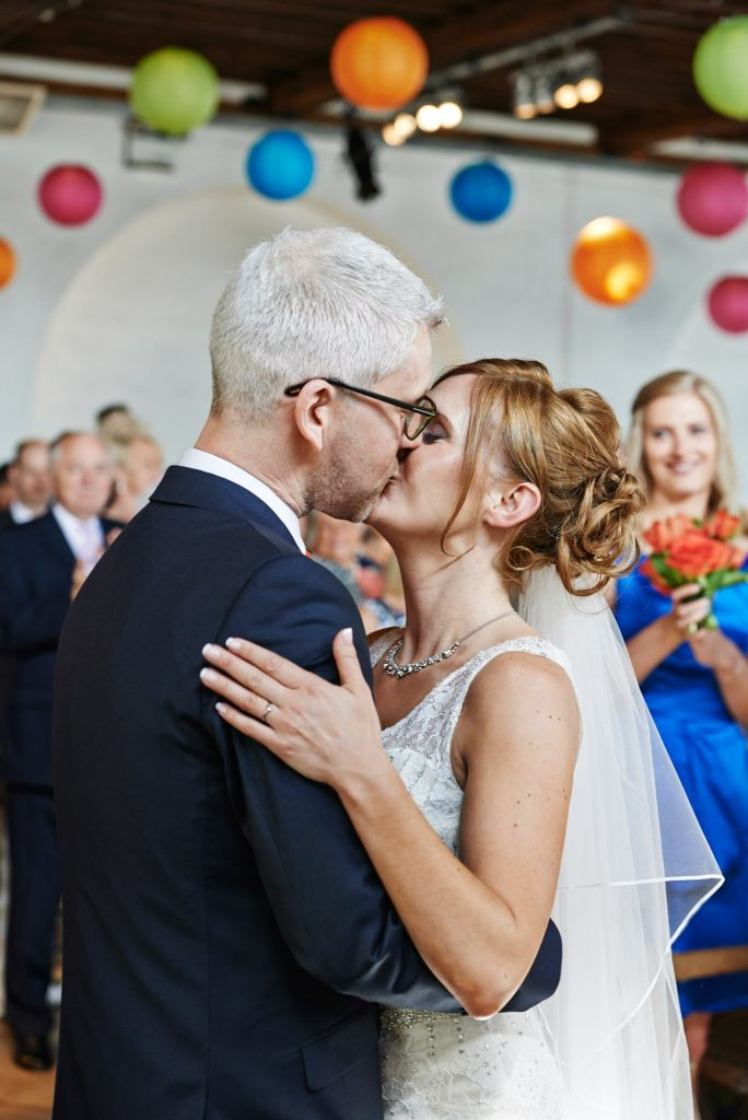 Wedding couple kissing during ceremony at Trinty Bouy Wharf Warehouse Wedding Venue