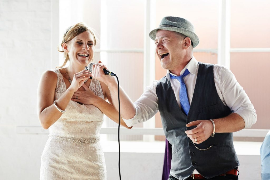 Bride and performer singing together during warehouse wedding at The Chainstore