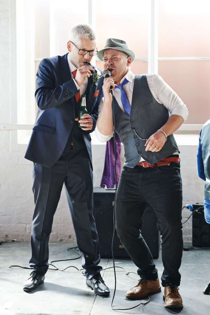 Groom and performer singing together during unique warehouse wedding